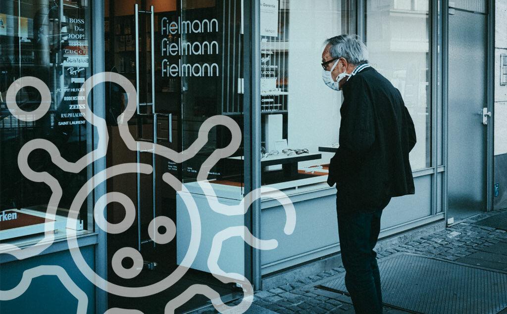 älterer Mann steht vor einem geschlossenem Geschäft