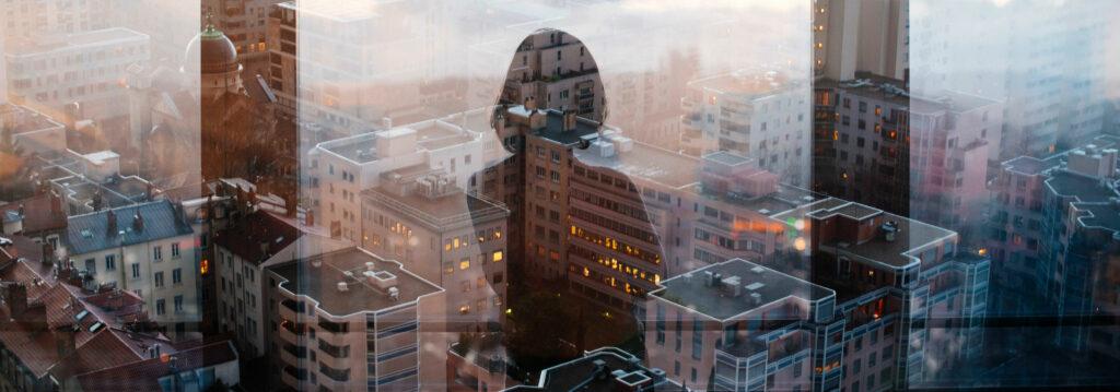 Spiegelbild einer Frau vor einer Skyline